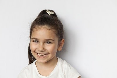 Portrait of a happy smiling latin child girl on white background
